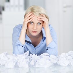 Tired executive With Crumpled Paper Balls At Desk